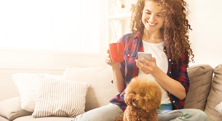 Mulher sentada no sofá da sua casa tomando um café e segurando o seu pet no colo